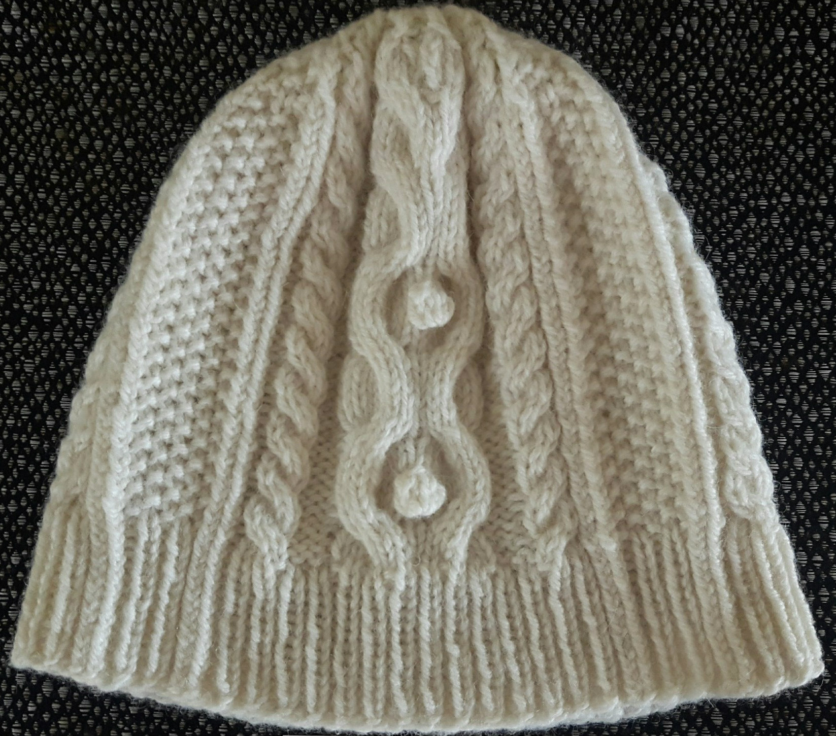 The pattern is available on Ravelry  https   www.ravelry .com patterns library cabled-aran-hat-with-beanie-variation db9d8b9b1da